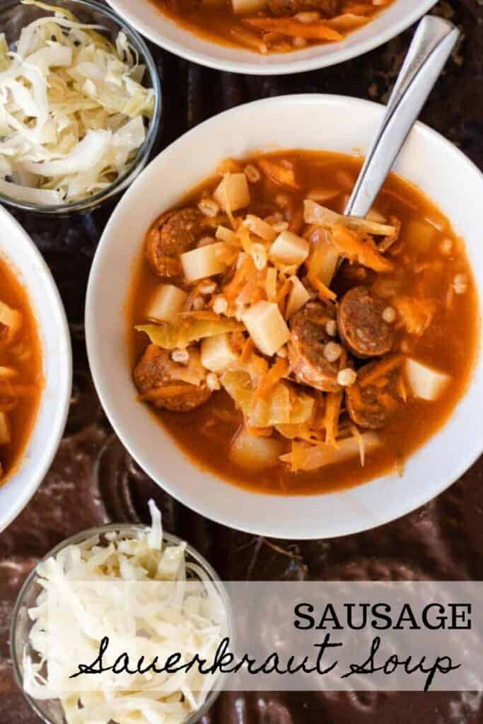 bowl of sauerkraut soup with sausages with a spoon in the bowl. Two glass bowls of sauerkraut sit next to the bowl of soup