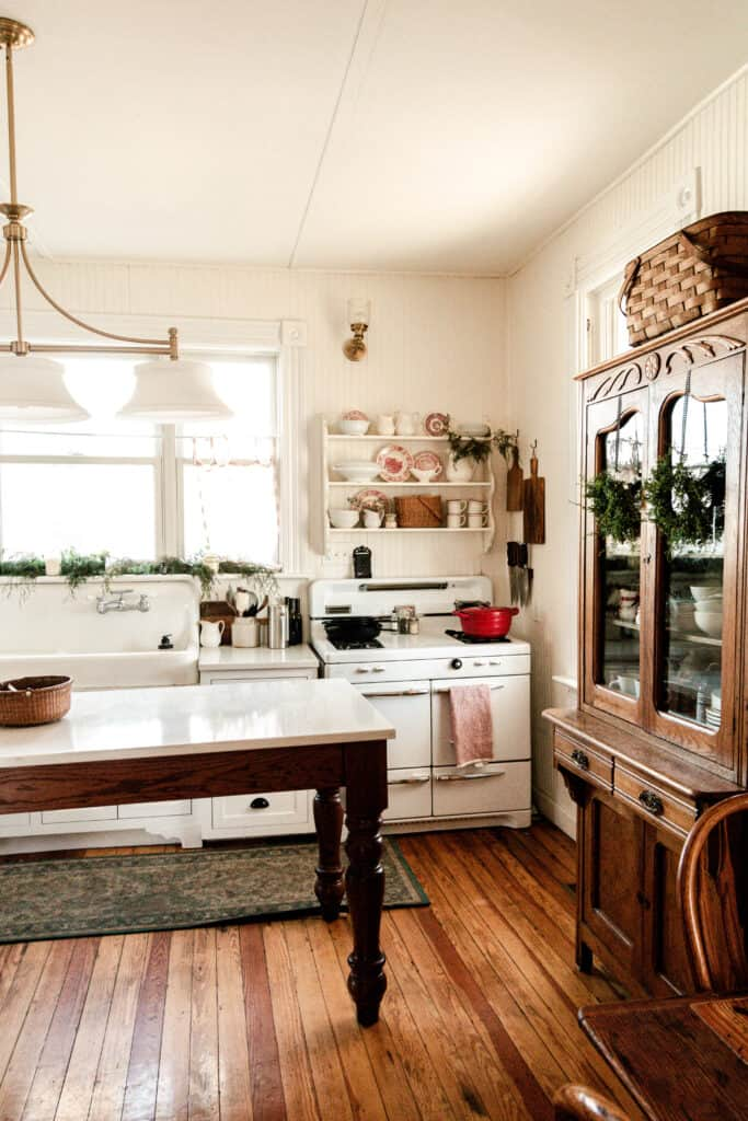 farmhouse kitchen decorated for Christmas with white and red plates sitting on the shelves over the stove. Greenery is layed on the window sill and wreaths hanging from china cabinet.