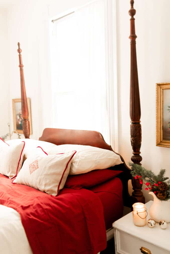 victorian bed with red and white linens. While linen pillows with red piping and a red decal in the middle sit on top of the bed