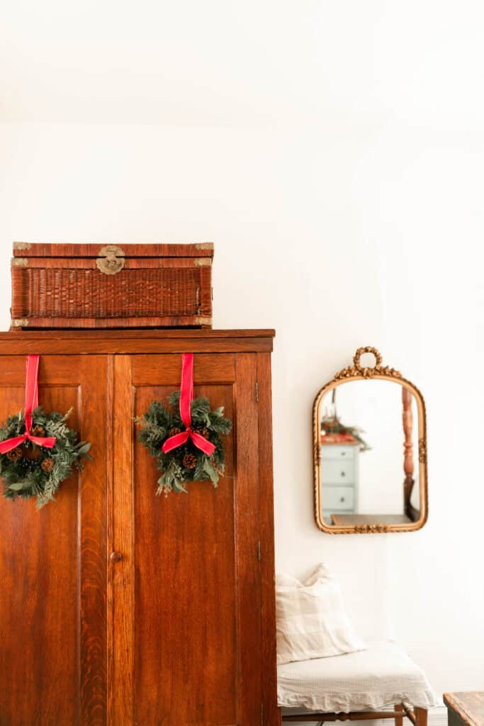 wood antique armoire with two greenery wreaths hanging with red ribbon. A gold mirror hangs to the right above a vintage bench