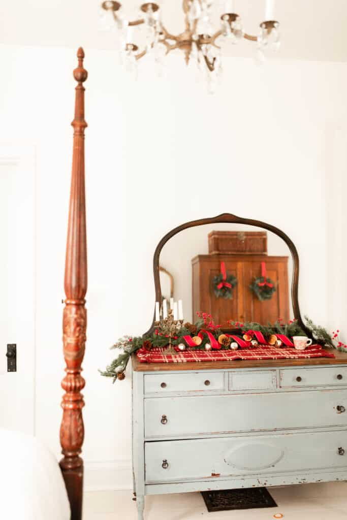 antique blue dresser decorated for Christmas with a red plaid runner, garland, red and gold ribbon, and bells