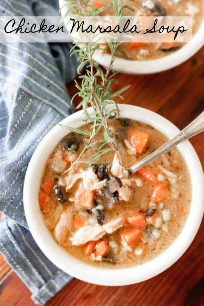 overhead photo of chicken Marsala Soup in two white bowls with a fresh spring of rosemary on top