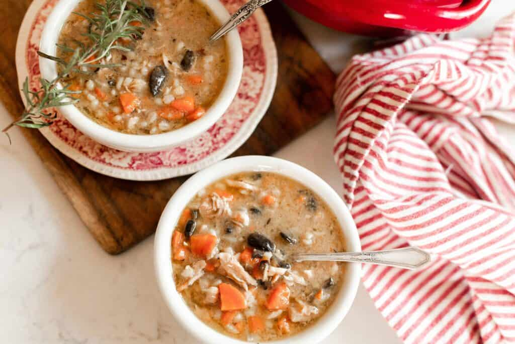 two bowls of chicken Marsala Soup. One bowl is on a red and white antique dish on top a wooden cutting board. A red and white stripped towel sits to the right