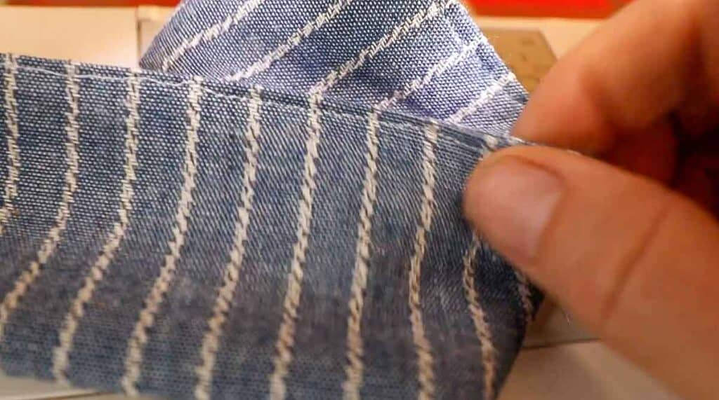 women hand showing a top stitched strap