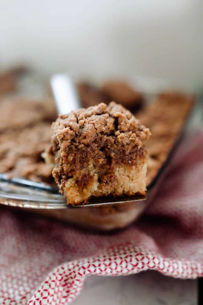 slice of coffee cake resting on top of baking dish of cake on a red and white towel