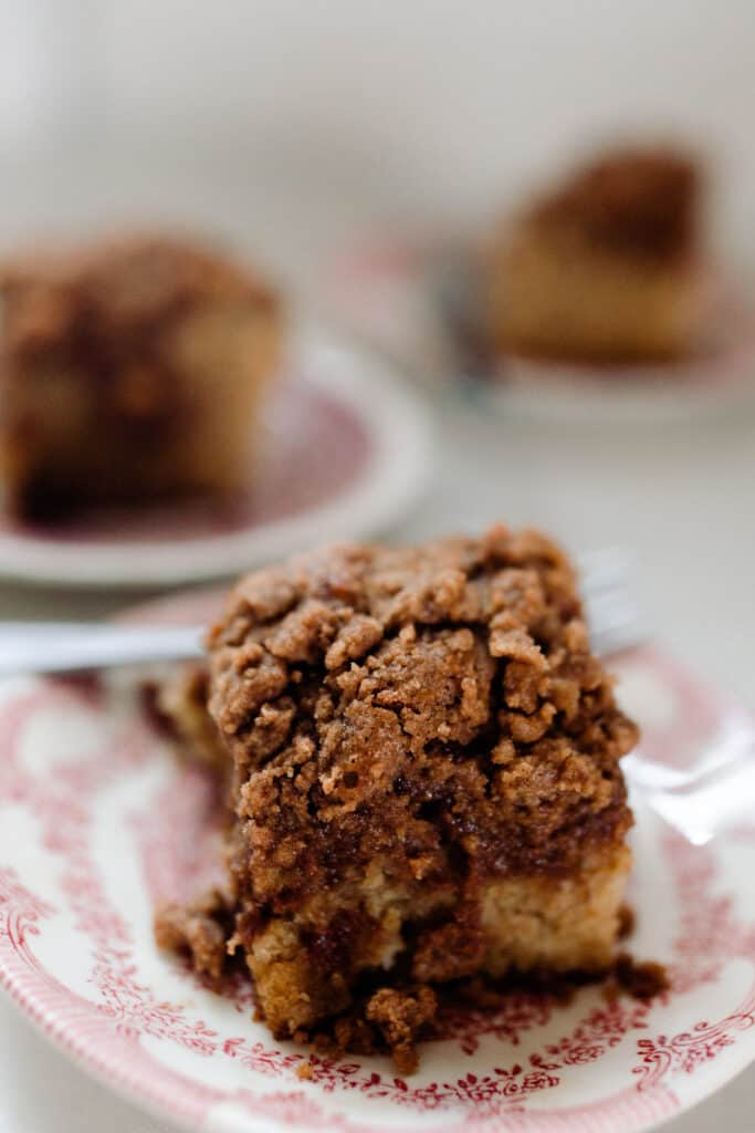 sourdough coffee cake with cinnamon crumble on a white and red vintage plates