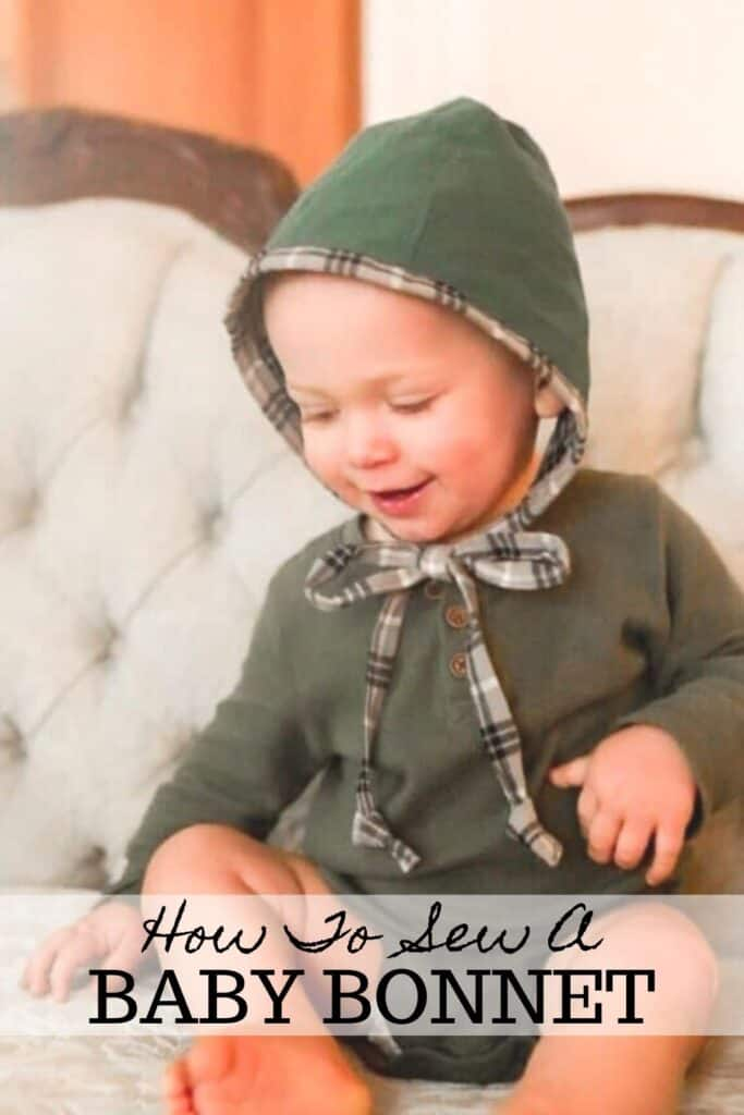 little boy smiling wearing a baby bonnet on a victorian couch