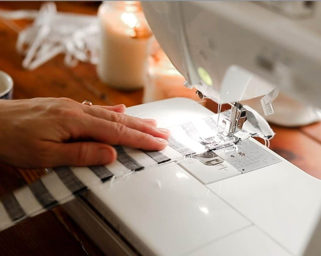 sewing a long piece of fabric that is folder over together to make a scrunch