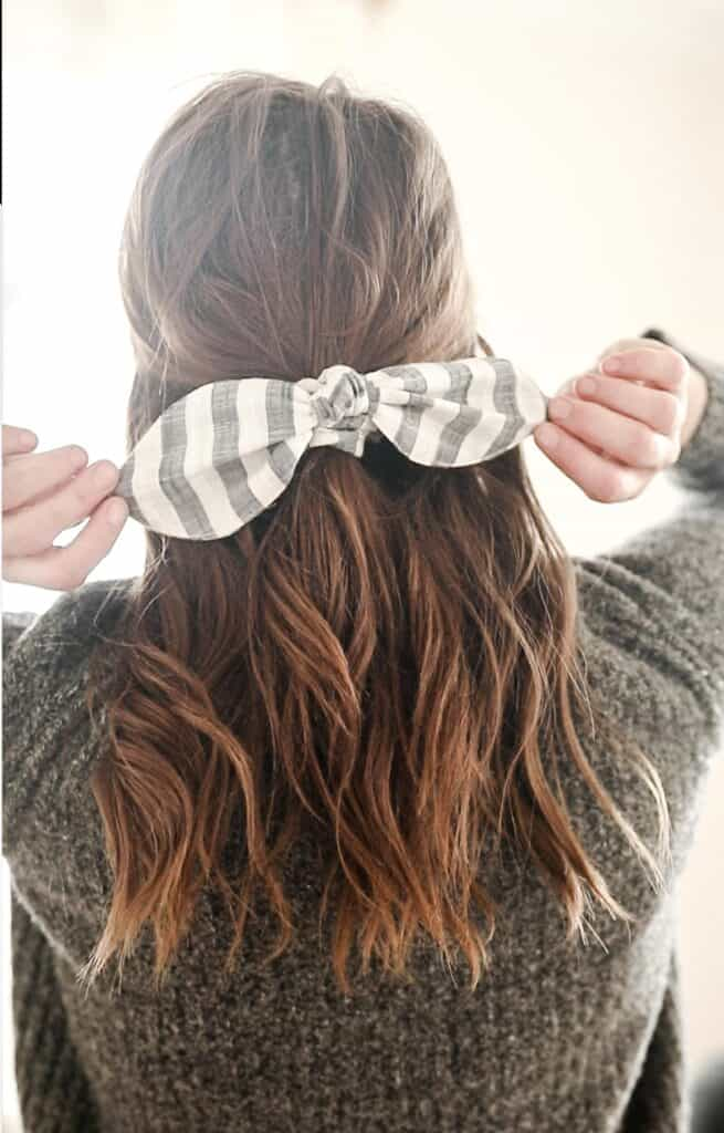 women with a gray sweater with her hair tied half up with a DIY scrunch bow