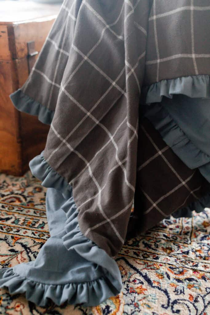plaid and blue double sided flannel blanket with ruffles drapped over a chair wit