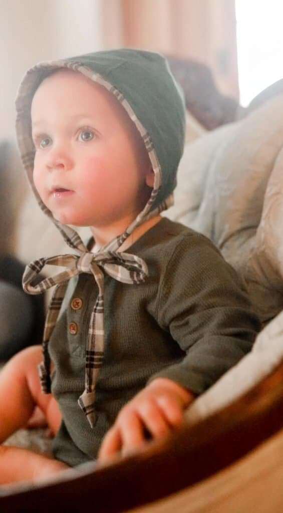 boy wearing a green long-sleeved onesie with a baby bonnet on