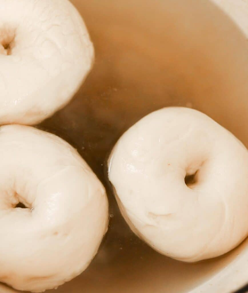 bagels being cooked in a pot of water, baking soda, and sugar