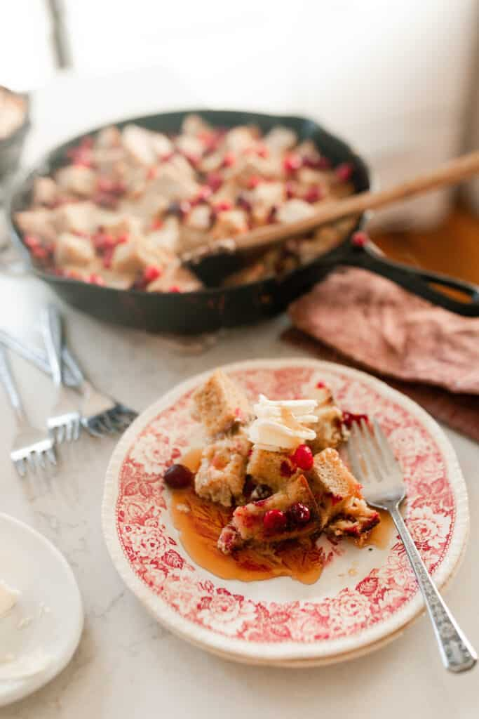 cranberry French toast casserole on a red and white antique plate with a fork. A cast iron skillet with more casserole in the background.