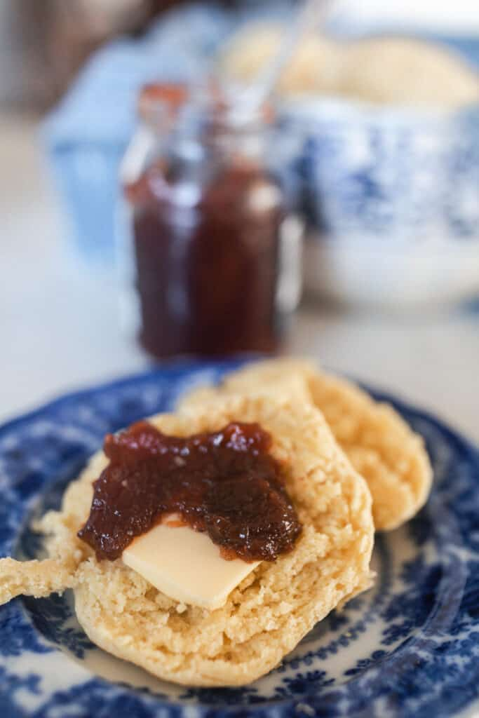 einkorn biscuits covered in butter and jam on a blue and white antique plate with jam and a bowl of biscuits in the background