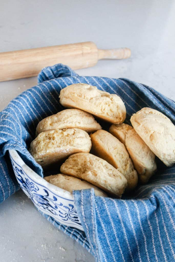 einkorn biscuits in a antique bowl lined with a blue and white stripped towel and a rolling pin in the background