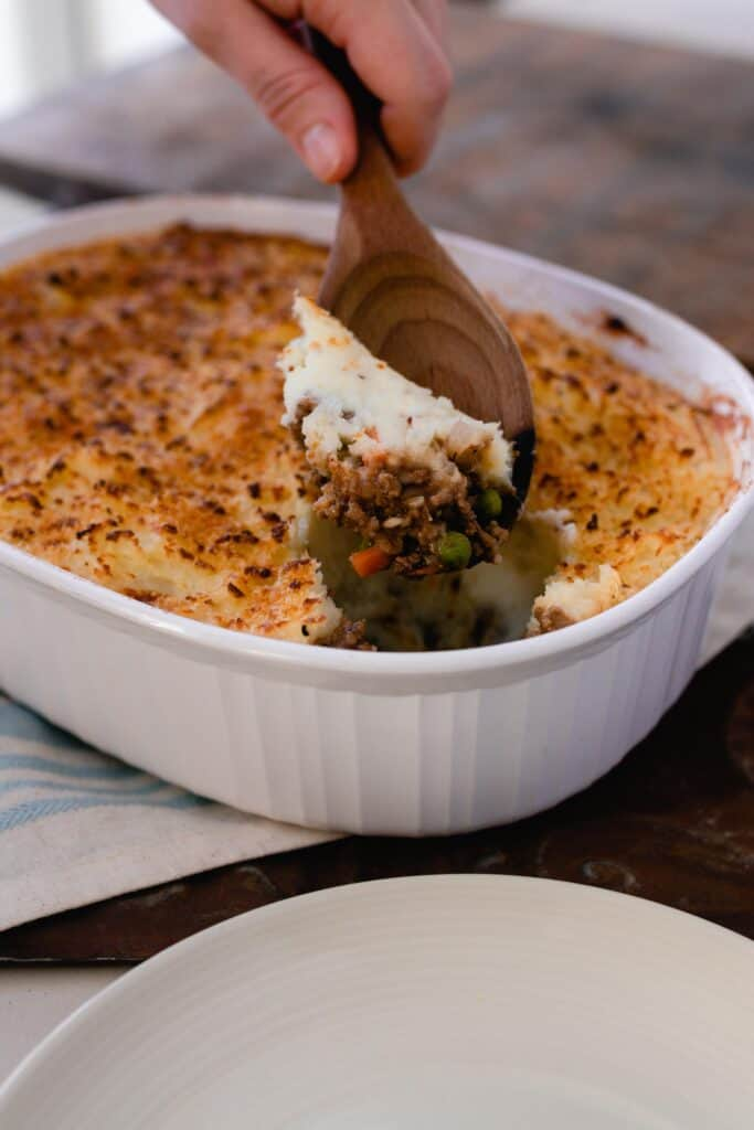 wooden spoon scooping out a baking dish of shepherd pie