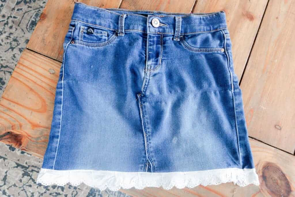 denim jeans turned into a skirt with a white eyelet trim laying flat on a wood table