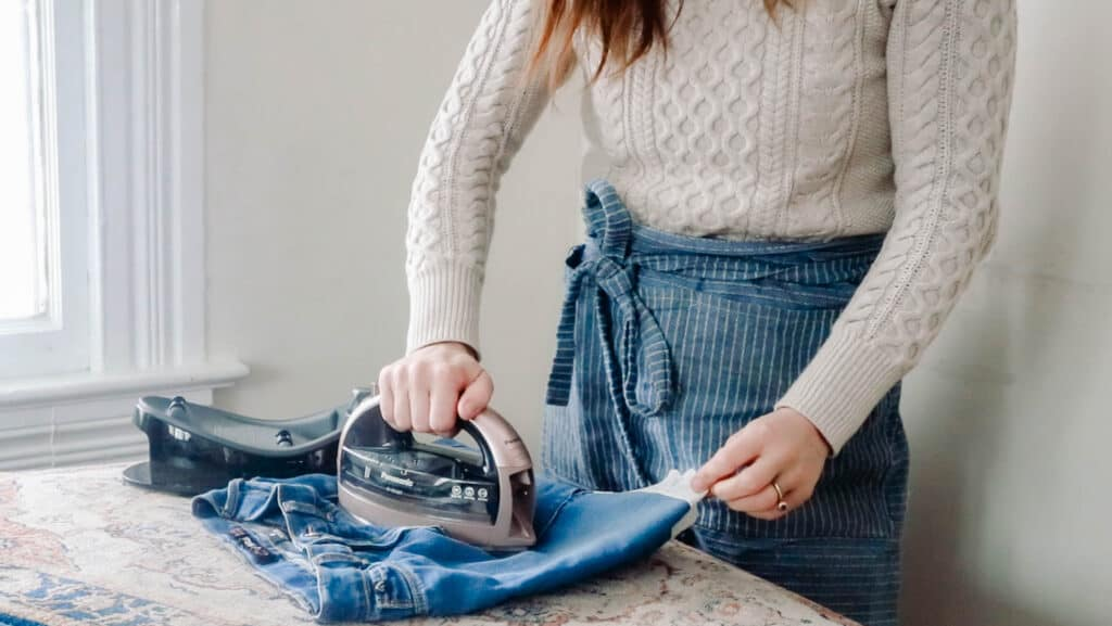 women pressing a jean skirt made from jeans on a table top