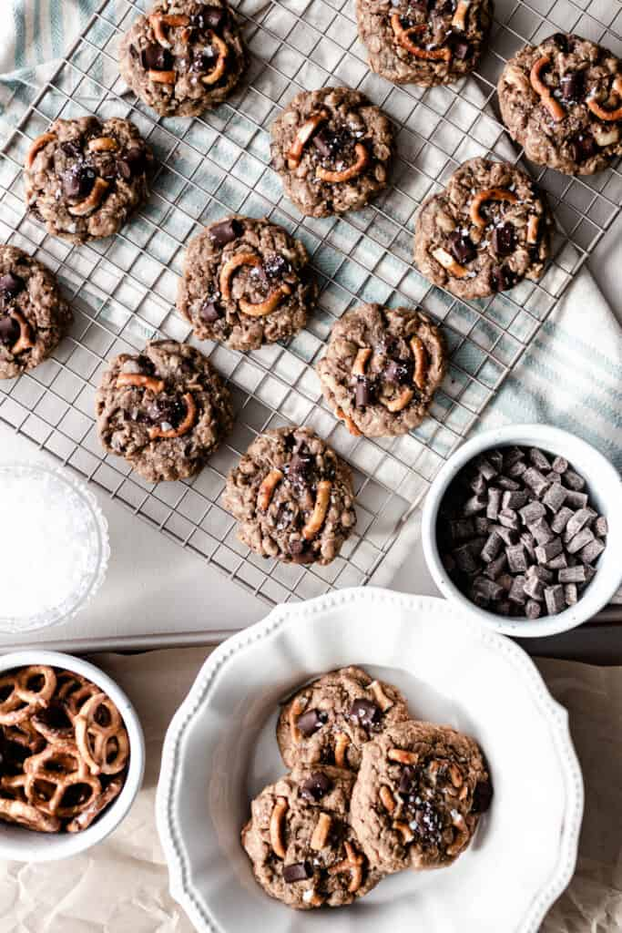 overhead photo lactation cookies on a cooling wrack. A plate of cookies sits right in front of the cooling rack and two containers of chocolate chunk and pretzels.