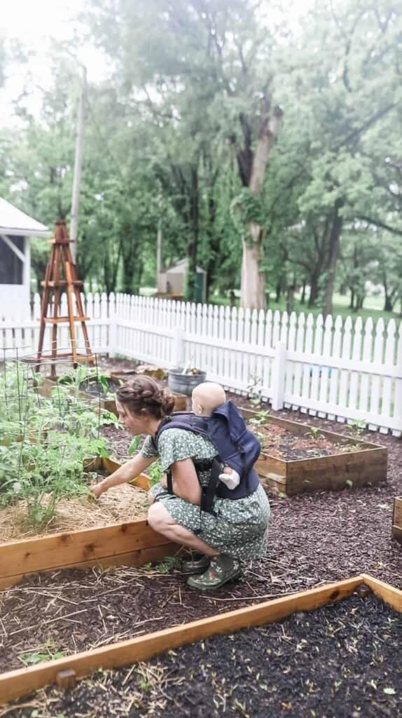 women with a baby on her back checking her garden