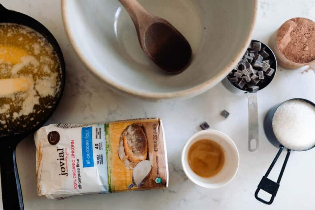 einkorn brownie ingredients around a large white bowl with a wooden spoon inside.