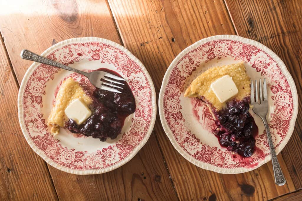 overhead photo of two vintage plates with einkorn puff pancakes topped with berry syrup with forks on a wooden table