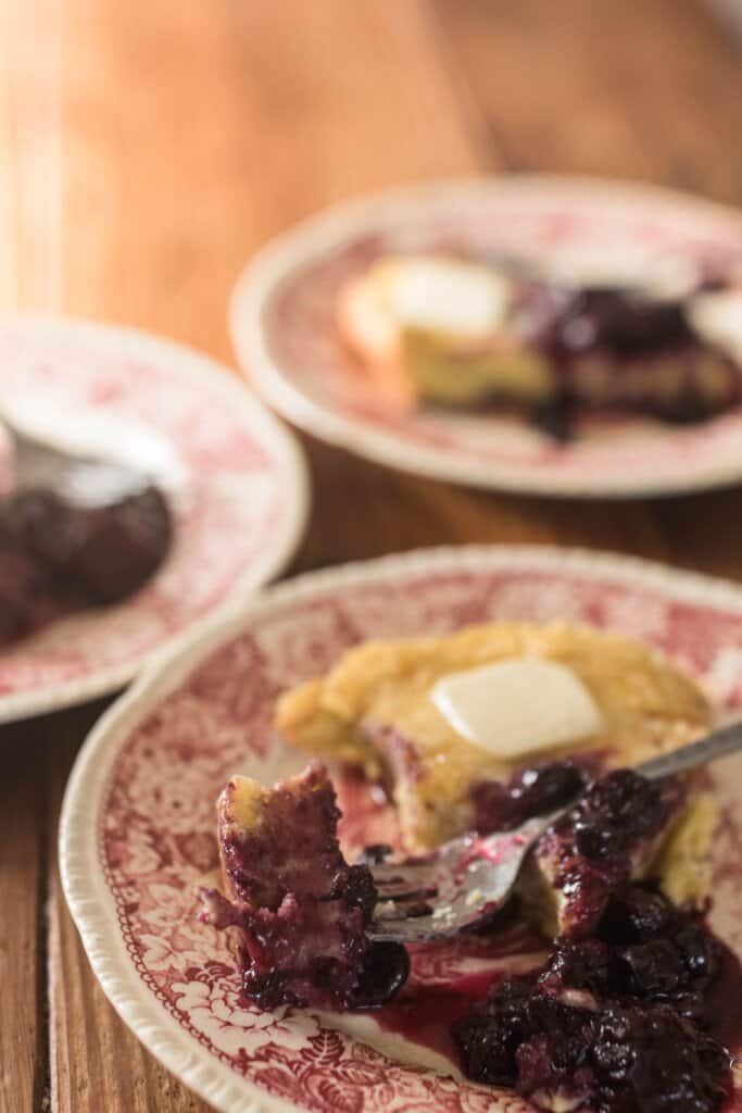 three plates of einkorn dutch baby pancakes with berry syrup on a wooden table