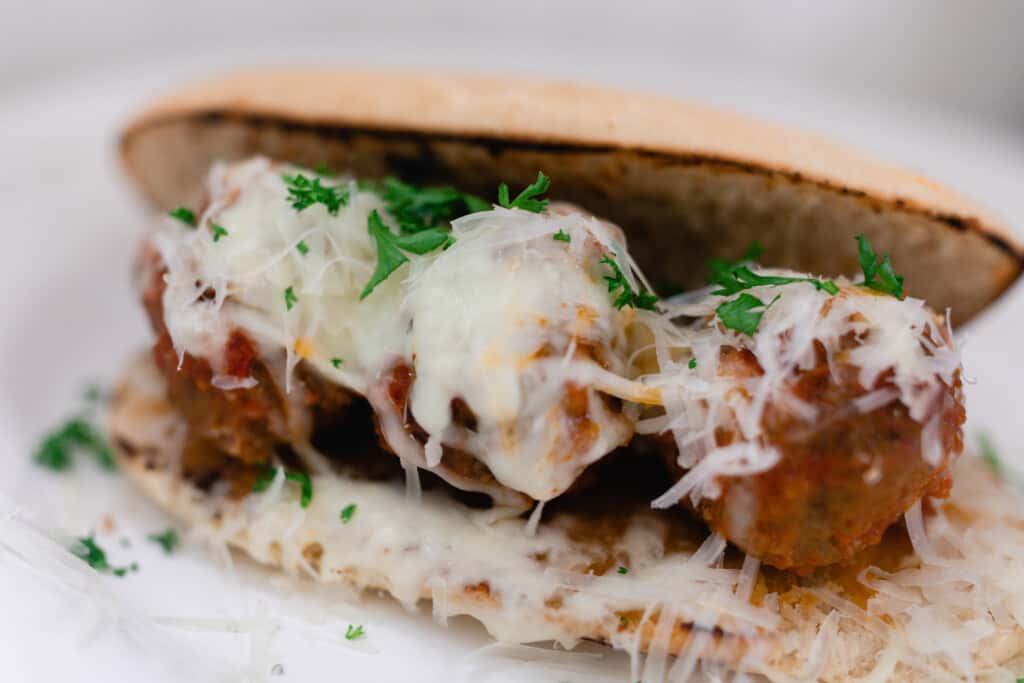 homemade meatball sub with three meatballs on sourdough bread covered in cheese and sprinkled with parsley