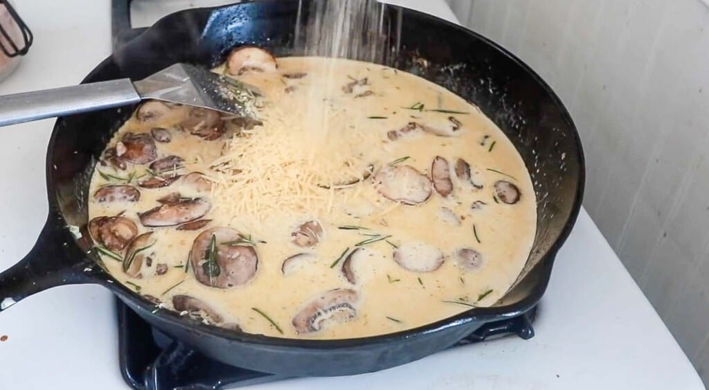 parmesan being added to creamy mushroom sauce in a cast iron skillet