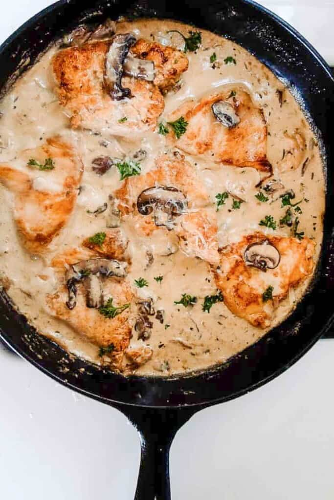 cast iron skillet with creamy mushroom chicken sauce with herbs