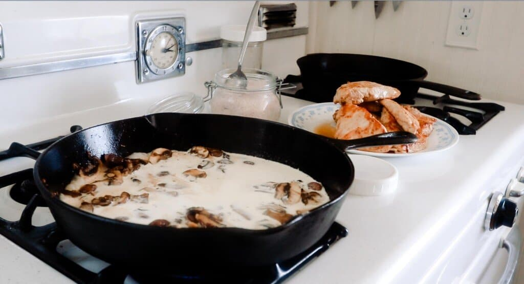 cream added to mushrooms in a cast iron skillet on an antique stove