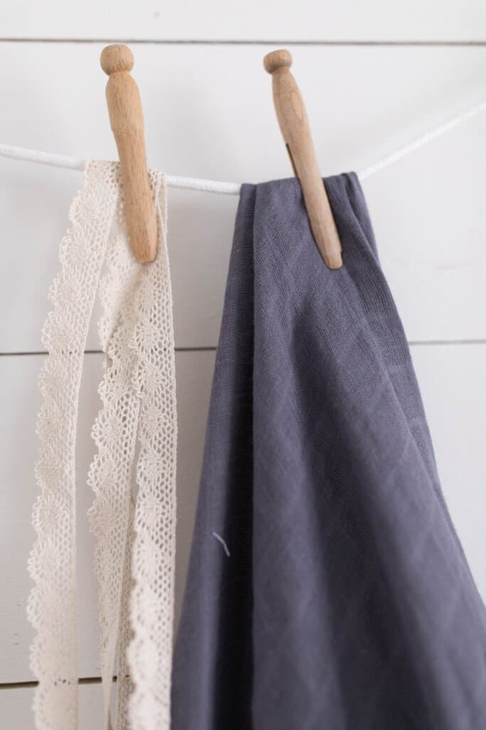 gauze fabric and lace hanging with a clothes pin against a shiplap wall