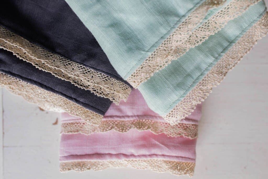 3 swaddle blankets with lace folded up on a white table