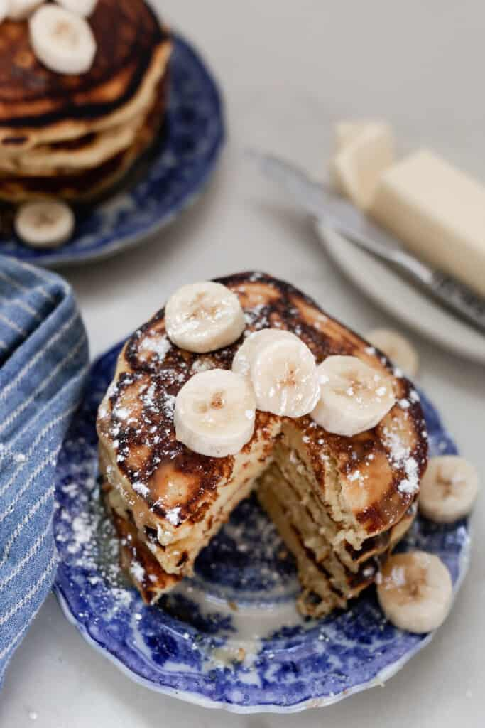 stack of einkorn pancakes topped with bananas with slice taken out of the stack. Butter on a dish with a knife to the right