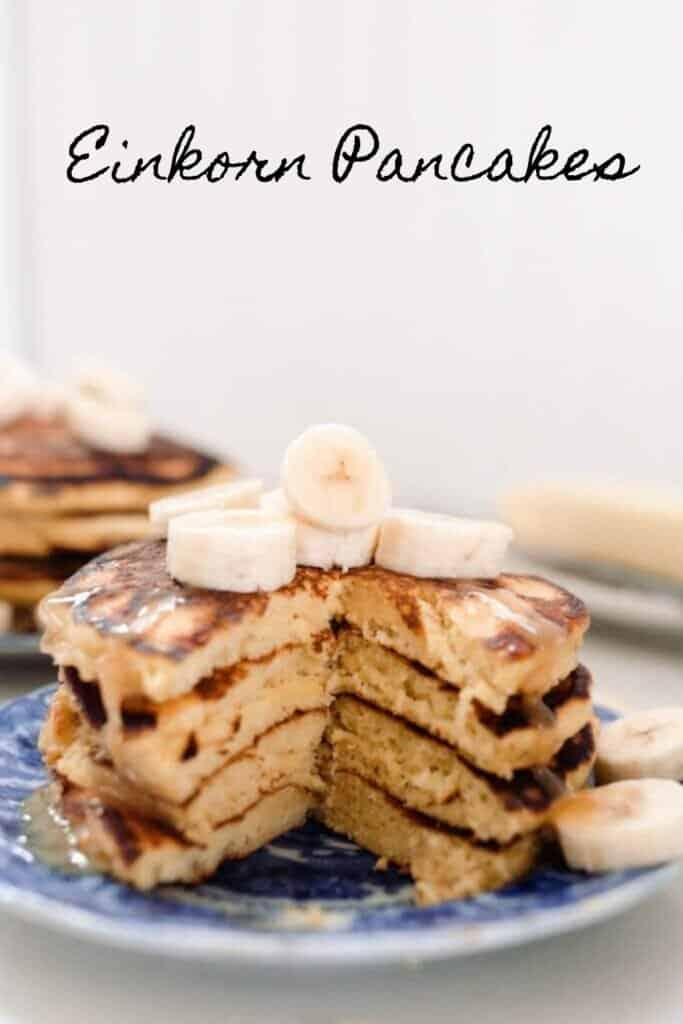 stack of einkorn pancakes topped with bananas on a blue and white antique plate. Butter on a dish is in the background