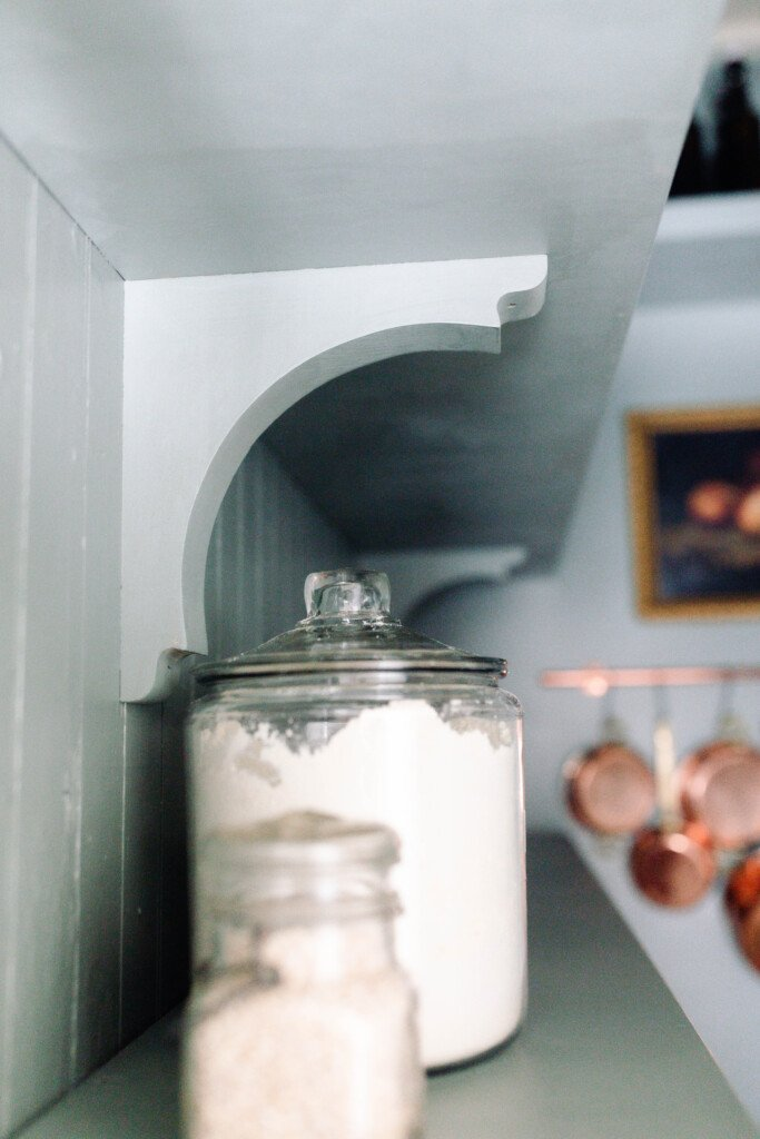 jars of flour on a wooden shelve with another shelf hung with corbels above
