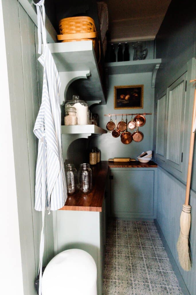 farmhouse pantry reveal with custom cabinetry with dark wood stained countertops, shelving, patterned tile, and copper pots hanging on the wall.