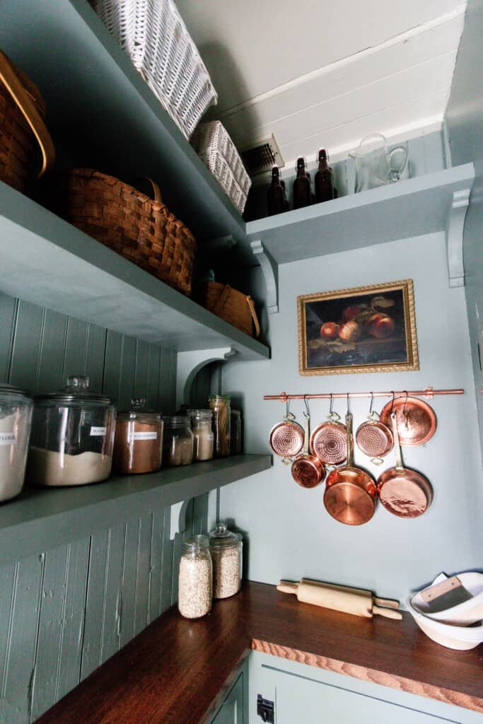 blue green painted shelves with corbels with jars and baskets lining the shelves. copper pots hand on a copper pot hanger with a peach painting in a vintage frame hangs above it.