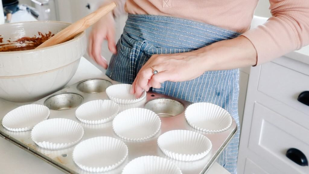 women wearing a blue apron placing cupcake liner into muffin tin wells