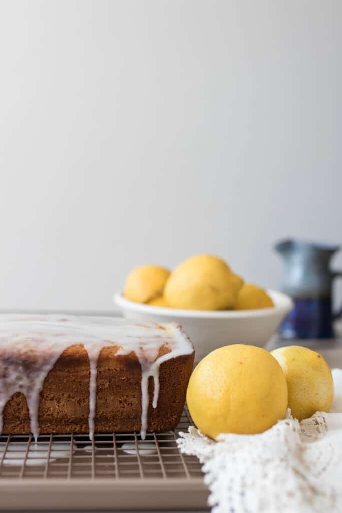 sourdough lemon pound cake drizzled with lemon icing on a wire rack. A bowl of lemons sit to the right
