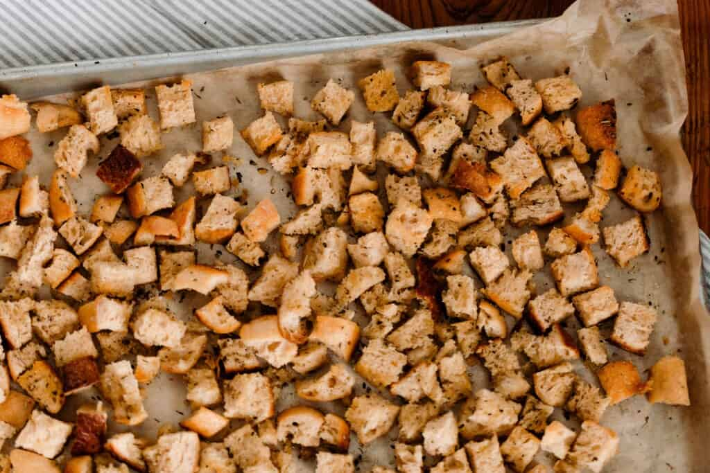 golden and crunchy sourdough croutons on a parchment lined baking sheet